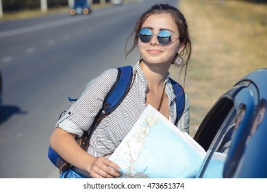 Travel - young woman with car look at road map on a highway against sky