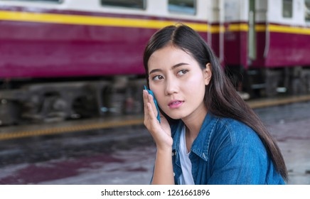 Travel young woman feels tired and hot use facial oil clean film sweating oil on her face at train station. Young girl using blotting paper removal oil for face fresh skin feeling so fresh and clean.
