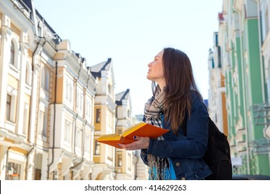 Travel. Young woman traveler with a backpack on her shoulder. Independent travel and out sightseeing in a history city. Student woman, her vacation. Learning foreign languages in a different country.