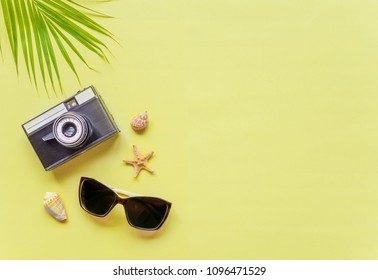 Traveler accessories: green tropical palm leaf, photo camera, seashells and sunglasses are on yellow background with copy-space. Top view travel or vacation concept, flat lay summer background