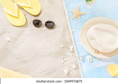 Traveler accessories on sand. Straw hat, sunglasses, flip flops, cocktail, sunblock with copy space. Travel vacation concept. Summer background