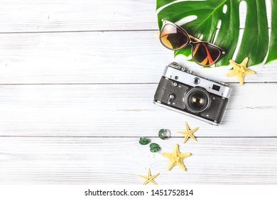 Traveler accessories, tropical monstera leaf on white wooden background with space for text. Travel vacation concept. Summer background. Flat lay. Top view.