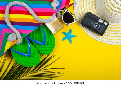 Traveler accessories, tropical palm leaf branches on yellow background with empty space for text. Travel vacation concept. Summer background. Road frame set. Flat lay, top view