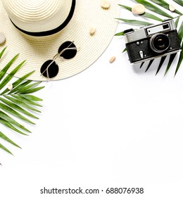 Traveler accessories, tropical palm leaf branches on white background with empty space for text. Travel vacation concept. Summer background. Road frame set. Flat lay, top view.
