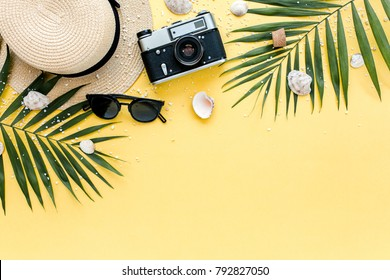 Traveler accessories, tropical palm leaf branches on yellow background with empty space for text. Travel vacation concept. Summer background. Road frame set. Flat lay, top view.