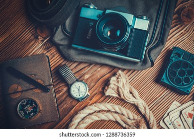 traveler or adventurer accessories on wood background. vacation concept