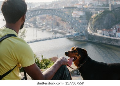 Traveler african man with dog enjoying city view in Porto, famous iron bridge and Douro rive on background