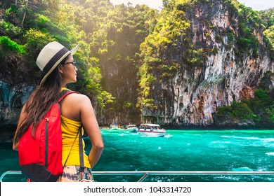 Traveler Aian woman relaxing on boat joy view of natural lagoon, Phi Phi island, Krabi, near Phuket, Travel Thailand, Beautiful destination place Asia, Summer holiday outdoor vacation trip