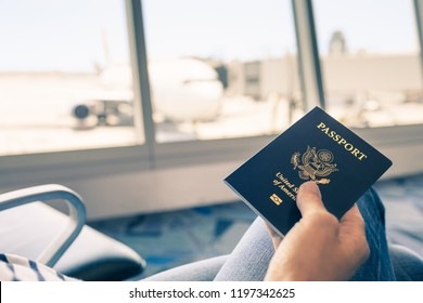 Traveler at airport holding United States passport in hand.