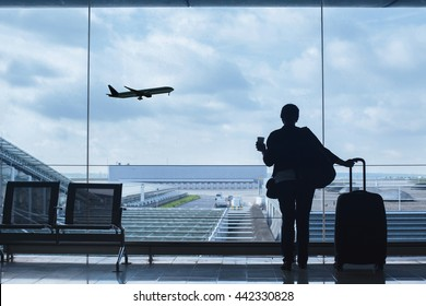 traveler in airport looking at the plane taking off