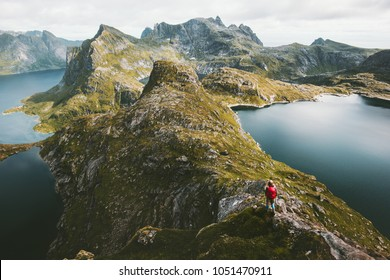 Traveler alone with backpack hiking on mountain ridge landscape hiking Traveling lifestyle adventure concept active vacations in Norway outdoor aerial view