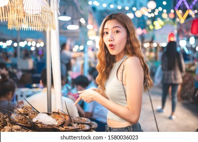 Traveler Asian blogger women travel in Bangkok, Thailand, beautiful female using .Travel vacation at night in the city concept, Young happy traveler asian woman  and backpack walking