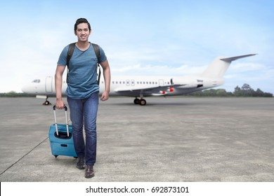 Traveler asian man get off the plane with suitcase in the airport
