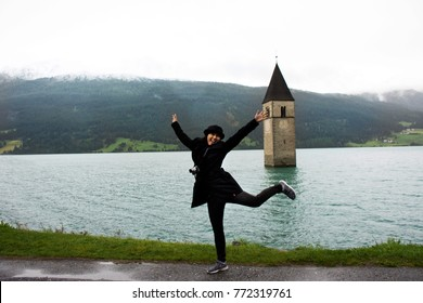 Traveler asian thai woman travel and posing for take photo at Submerged tower of reschensee church deep in Resias Lake in Trentino-Alto valley or Alto Adige in Bolzano or bozen city at Italy