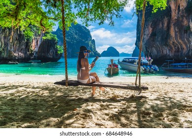 Traveler asian woman in bikini relaxing on wooden swing under tree and using tablet on tropical beach, Koh Lao Lading island, Andaman sea, Krabi province, Travel in Thailand