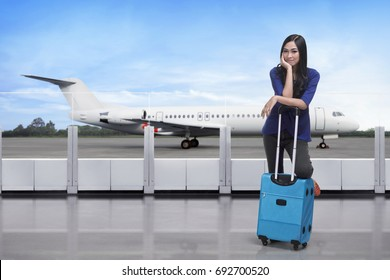 Traveler asian woman standing with suitcase on the terminal airport
