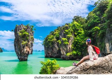 Traveler Asian woman in summer dress relaxing on rock joy view of James Bond island, Phang Nga bay, near Phuket, Travel Thailand, Beautiful destination landscape Asia, Holiday outdoor vacation trip
