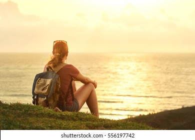 Traveler with backpack enjoying sunset listening to music on peak of mountain.