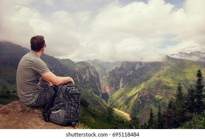 Traveler with backpack enjoying view mountain gorge Ma Pi Leng. Province Ha Giang, North Vietnam.Mountains landscape, travel to Asia, happiness emotion, summer holiday concept