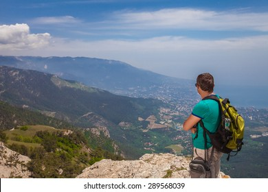 Traveler with backpack enjoying a view of valley from the mountain tops