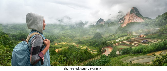 Traveler with backpack looks at the mountains and rice terraces in the rain in the North of Vietnam.