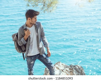 Traveler with backpack on the rocks near the sea looking away. Summer Travel Vacation. Handsome young caucasian tourist man in casual clothes outdoors on the nature.