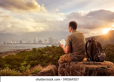 Traveler with backpack sitting on top of rock and reading a book on background of modern city.Summer vacations, traveling along mountains and coast, freedom and active lifestyle concept.