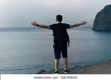 Traveler with backpack stand on the shore and looking at the ocean with raised hands in air
