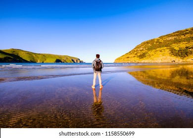 A traveler with a backpack stands along a beach. He is admiring the beautiful ocean, hills and landscape. He is also thinking about the meaning of life. The water has reflection of the sky.