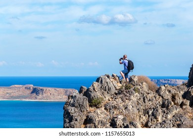 traveler with a backpack stands on a rock and takes pictures on the phone, Crete, Greece