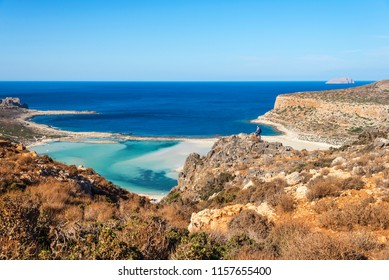 traveler with a backpack stands on a rock and looks at the panorama of the Balos beach, Crete, Greece