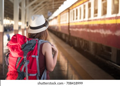 Traveler with backpack waiting for a train at train station. Travel and vacation concept.
