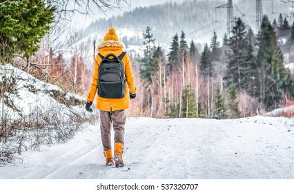 traveler with a backpack and yellow hat and knitted walking on snow covered road in winter forest in frosty weather. Space for text
