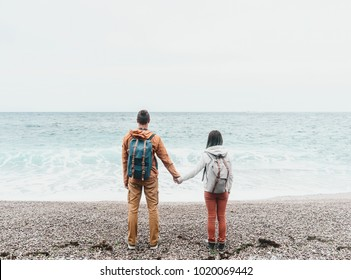 Traveler backpacker young couple in love standing on shore and enjoying view of sea.