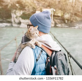 Traveler backpacker young man standing on bridge over river with cute cat.