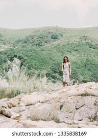 Traveler backpacker young woman walking in summer mountains on rocky terrain.
