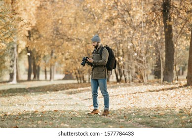 A traveler with a beard in aviator sunglasses with mirror lenses, olive military jacket, jeans, hat with backpack and wristwatch holds the DSLR camera and checks something in the smartphone