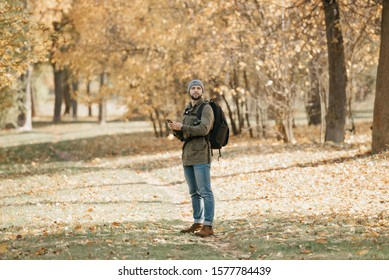 A traveler with a beard in aviator sunglasses with mirror lenses, olive military jacket, jeans, hat with backpack and wristwatch holds the DSLR camera and the smartphone looks away in the forest.