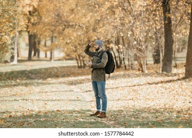 A traveler with a beard in aviator sunglasses with mirror lenses, olive military jacket, jeans, hat with backpack and wristwatch holds the DSLR camera and the smartphone. A Photographer looks straight