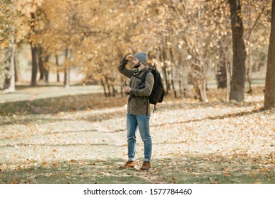 A traveler with a beard in aviator sunglasses with mirror lenses, olive military jacket, jeans, hat with backpack and wristwatch holds the DSLR camera and the smartphone. A Photographer looks for.