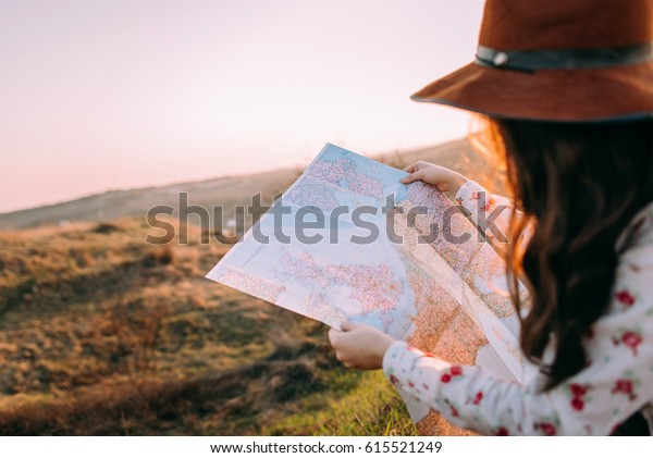 Traveler beautiful girl with a hat looking at a map at sunset sitting on a background of mountains. Concept photo travel, adventure. close-up