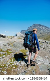 traveler with big backpack hiking on Besseggen ridge in Jotunheimen National Park, Norway