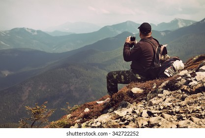 Traveler with binoculars sitting on top of a mountain and and looks into the distance at sunset. Filtered image:cross processed vintage effect.