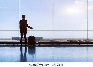 Traveler businessman in airport lounge waiting for the flight and standing with trolley luggage, business travel