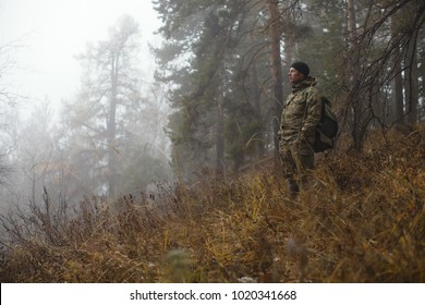 Traveler in camouflage clothes with a backpack observes the surroundings against the backdrop of a misty autumn forest in cold weather. Survival in the wild.
