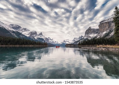 Traveler canoeing on Maligne lake with altocumulus clouds in Jasper, Canada