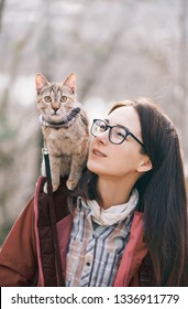 Traveler cat wearing in bandana sitting on shoulder of young woman outdoor.