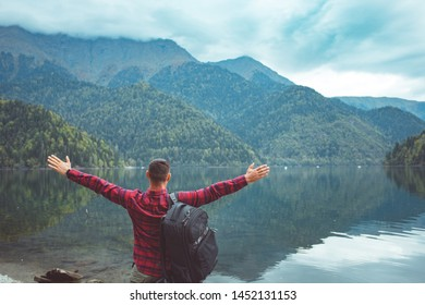 Traveler in checkered red shirt walk by the lake. Dude enjoy the view of the mountains and the forest.