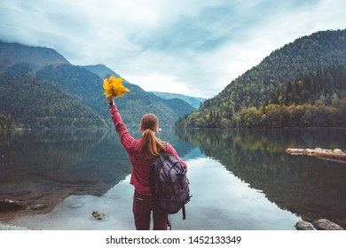 Traveler in checkered red shirt walk by the lake.  Girl enjoy the view of the mountains and the forest.