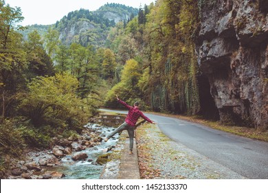 Traveler in checkered red shirt walk by the river. Dude enjoy the view of the mountains and the forest walking on the curb along the mountain road above the river.